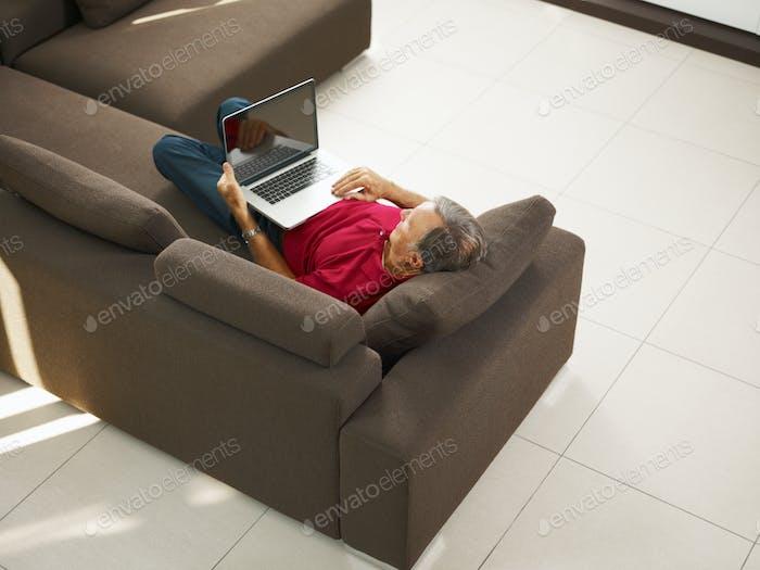 Senior Man Laying On Sofa Using Laptop Computer