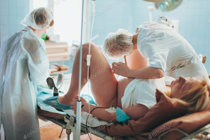 Im Krankenhaus Hebamme gibt Neugeborenes Baby an eine Mutter zu halten, Unterstützer Vater sitzt in der Nähe der Frau