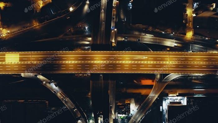 Top down Philippines illuminated traffic bridge road aerial. Cars, trucks drive at urban freeway