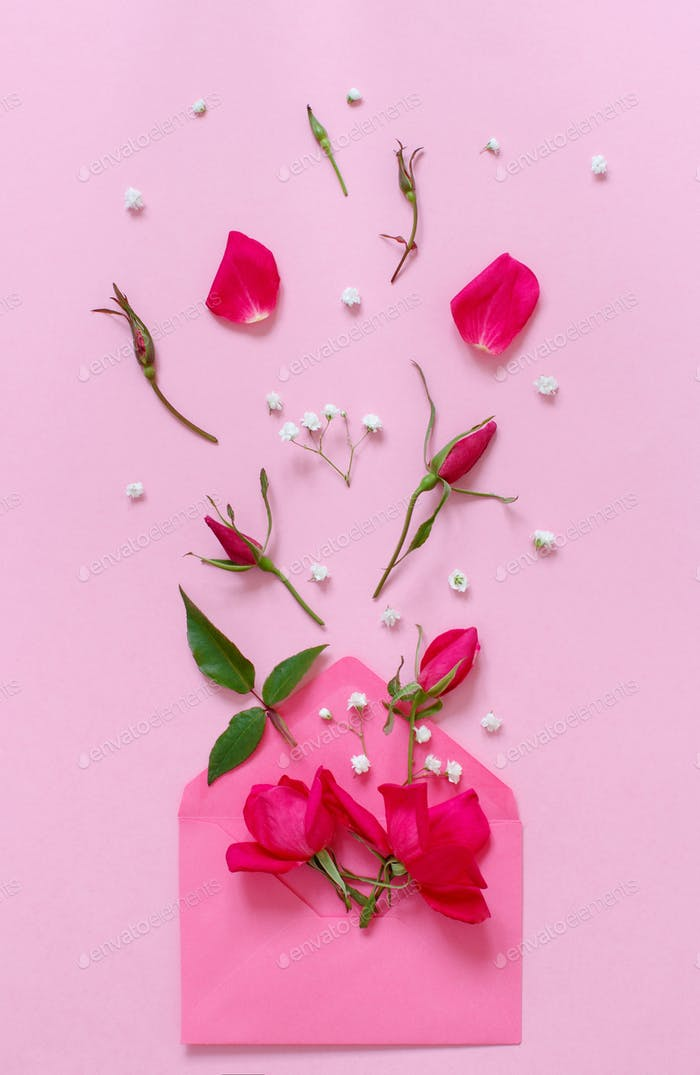 Spring composition with envelope and pink roses over pink background