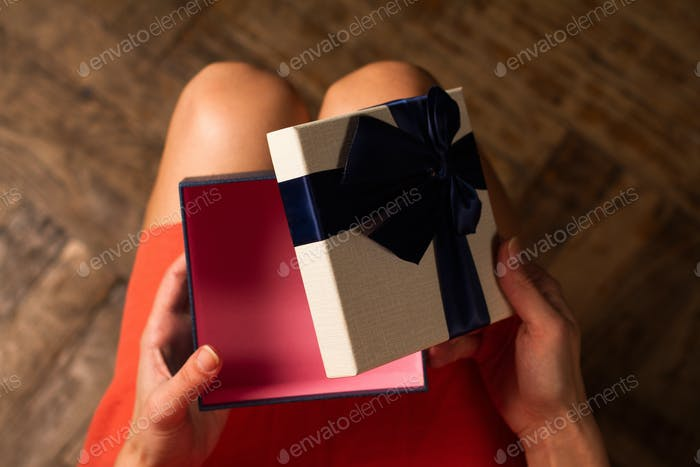 Woman opening a cardboard gift box with blue ribbon