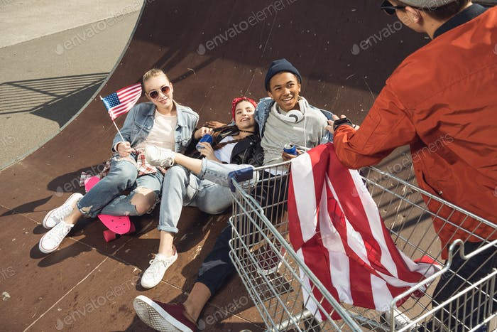 Teenagers Having Fun and Lying With American Flag in Skateboard Park, Hipster Style Concept