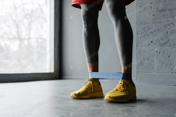 White sportsman doing exercise with expander stretch tape indoors