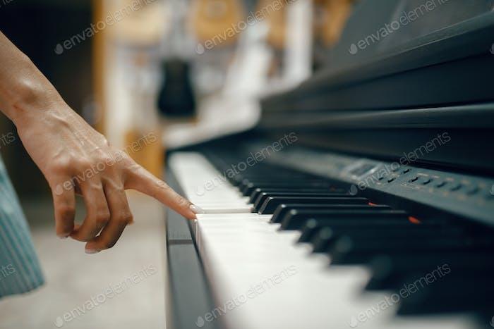 Young woman choosing digital piano in music store