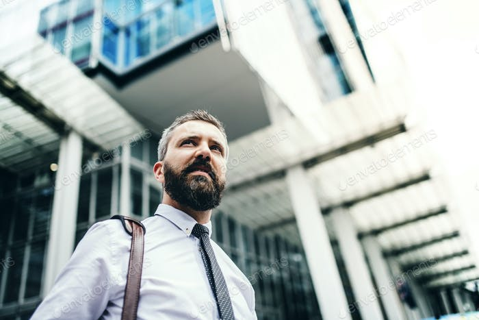 Low angle portrait of businessman standing on the street in city. Copy space.