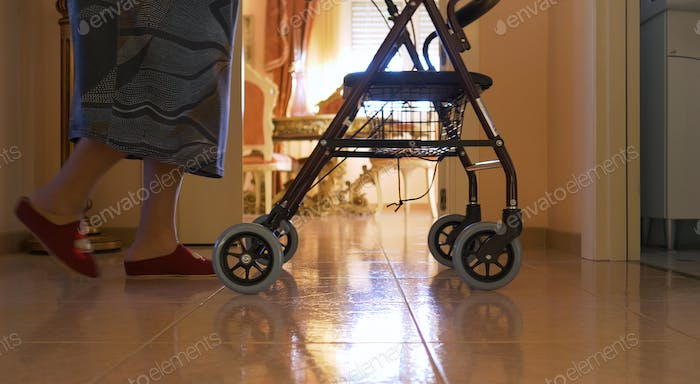 Elderly woman walks indoors with the walker. Detail of the legs and slow motion scene.