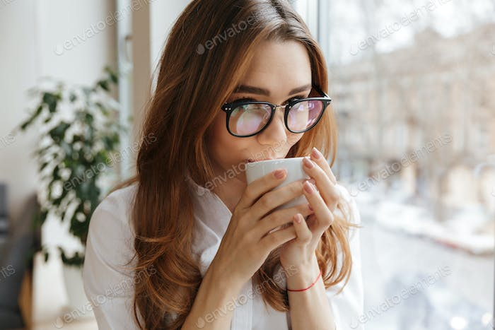 Cute business woman sitting indoors drinking coffee