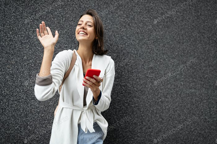 Young beautiful happy woman using smart phone