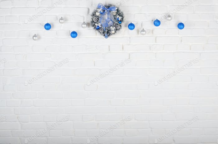 Christmas blue and silver balls and wreath on white brick wall h