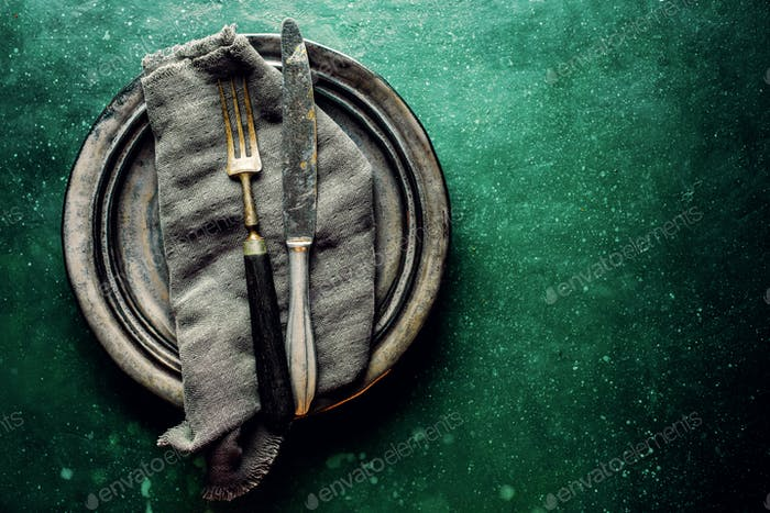 Vintage cutlery on plate on green table