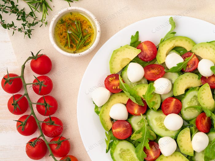 Fresh salad. Tomatoes, cucumbers, arugula, mozzarella, avocado. Fragrant oil with rosemary