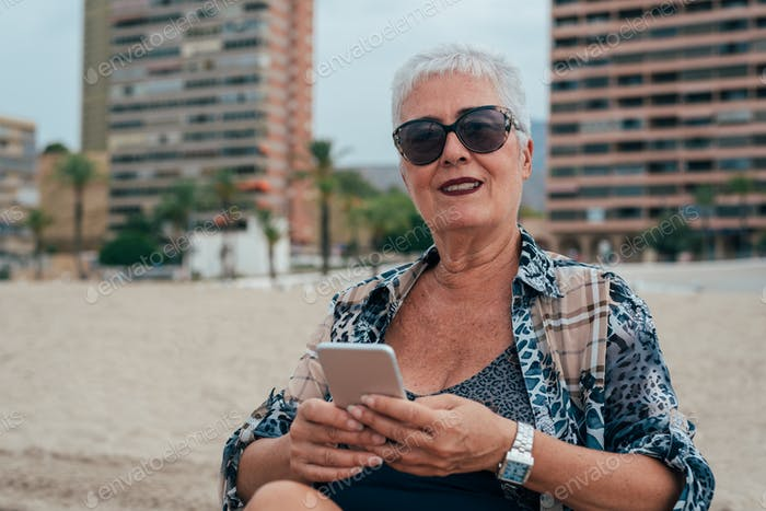 Elderly woman at the beach on the mobile phone
