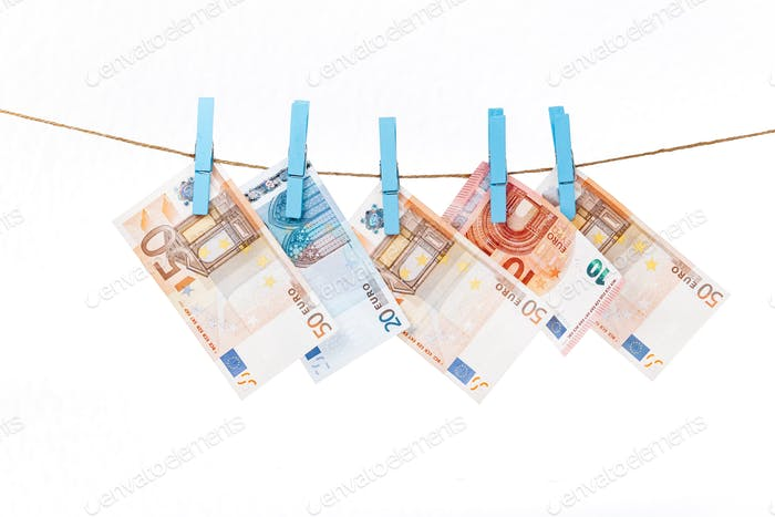 Euro banknotes are attached with blue clothespins to a rope on a white background