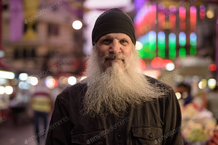 Face of mature tourist man with long beard in Chinatown at night