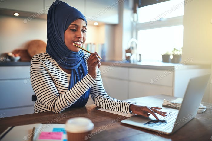Young Arabic female entrepreneur working from home in her kitchen