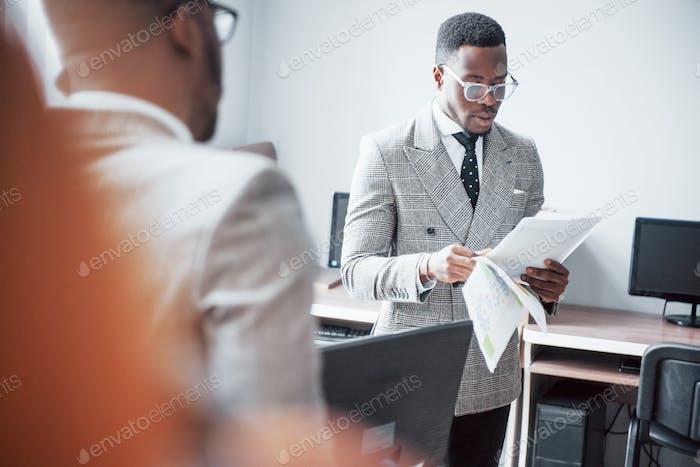 Moderner Geschäftsmann bei der Arbeit. Zwei selbstbewusste Geschäftsleute in Formalwear diskutieren etwas Während