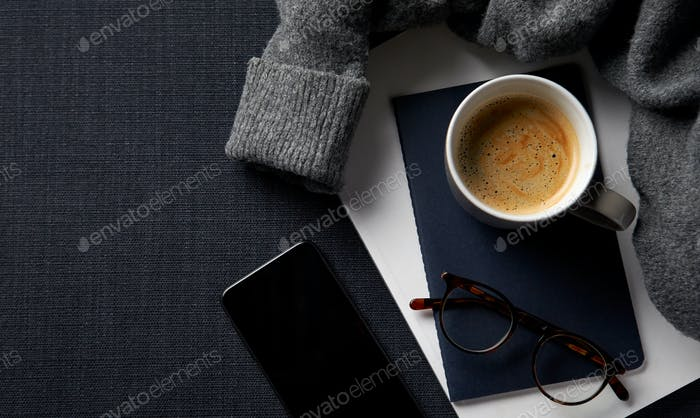Flache Lay Lifestyle Shot mit Jumper Notebook und Handy auf schwarzem Hintergrund