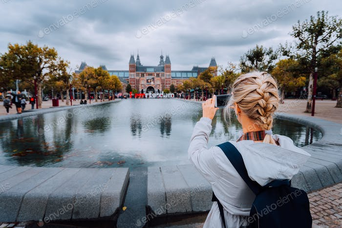Woman tourist taking photo of the Rijksmuseum in Amsterdam on the mobile phone. Travel in Europe