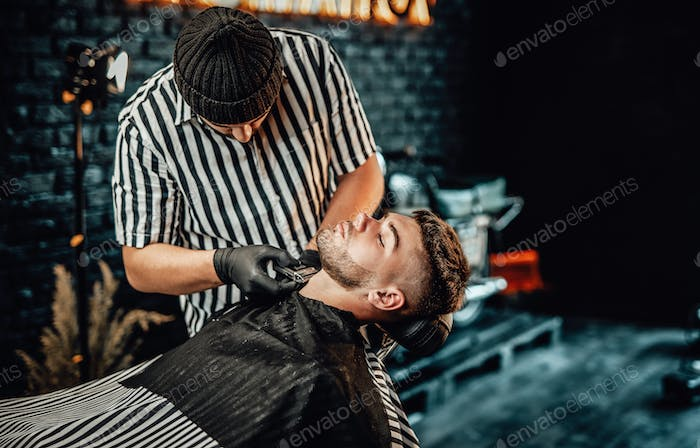 Skilled barber cutting his client's beard with clipper