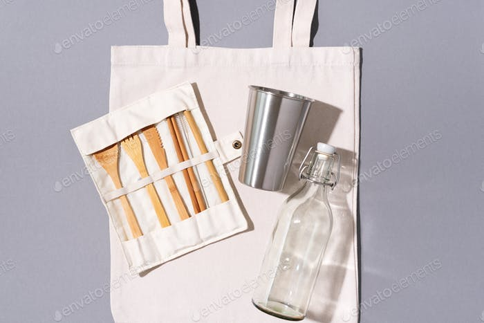 Cotton bags, glass bottle, metal cup, bamboo cutlery on gray background. Sustainable lifestyle. Zero