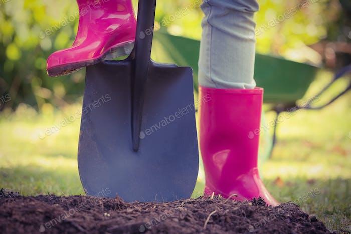 Frau hält Schaufel im Garten