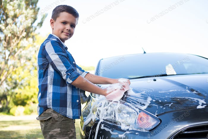 Teenage boy washing a car on a sunny day