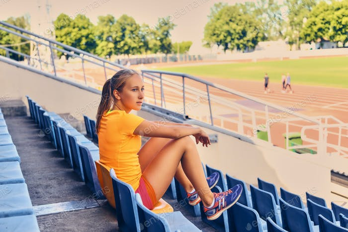 Blond sporty female runner to quick start position.