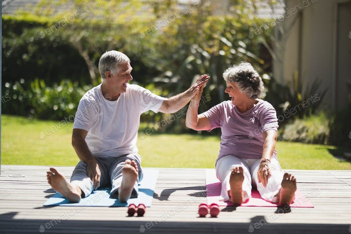 Cheerful senior couple giving high five while exercising together at porch