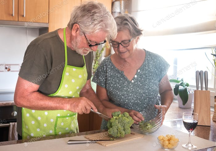 A senior couple together in the kitchen and the husband cuts and cleans the broccoli