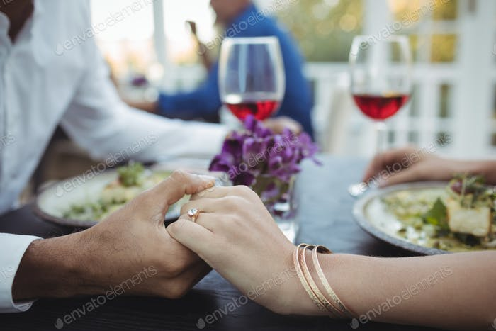 Couple holding hands while having meal