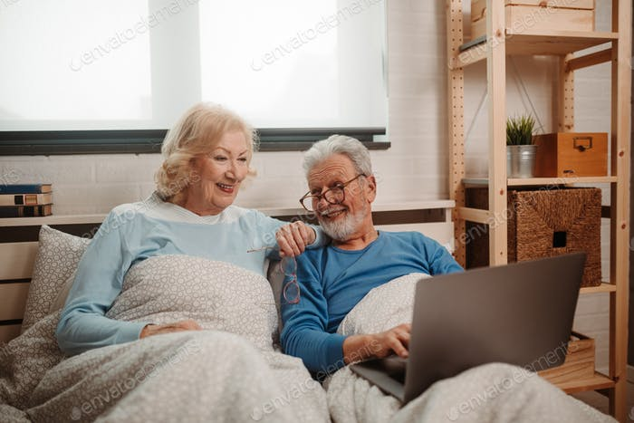 Portrait of lovely elderly couple lying in bed and having fun by using modern technology.