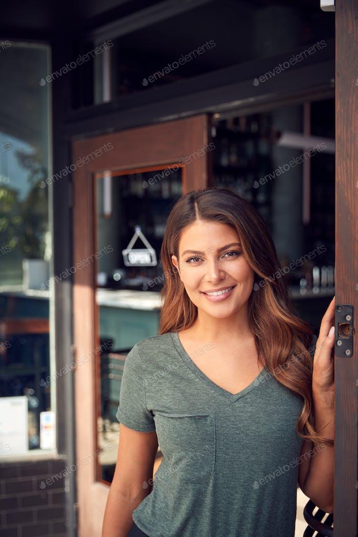 Portrait Of Female Owner Of Start Up Coffee Shop Or Restaurant Standing In Doorway