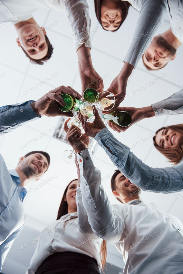 Vertical photo. View from below. Knocking glasses in the office. Celebrating success