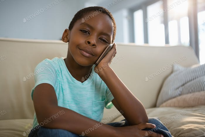 Boy talking on mobile phone in the living room at home
