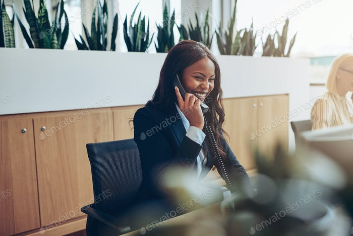 African American businesswomen talking on an office telephone and laughing