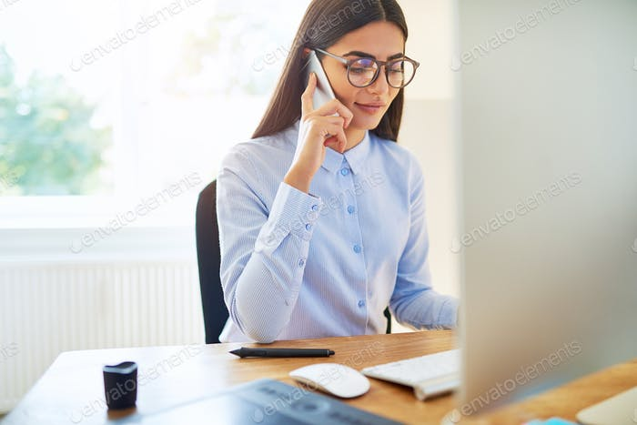 Young businesswoman in glasses talking on a mobile