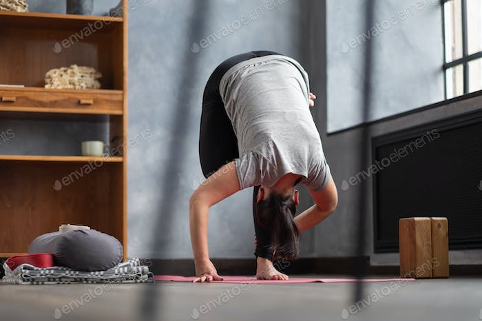 Woman working out indoors standing in Uttanasana during online lesson.