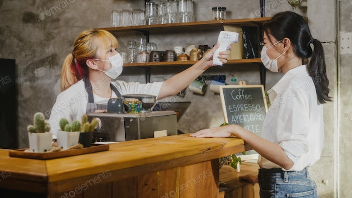 Young Asia female restaurant staff wearing face mask using infrared thermometer check before enter.