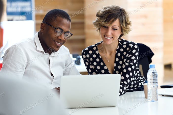 Group of smiling young businesspeople working with laptop on cow