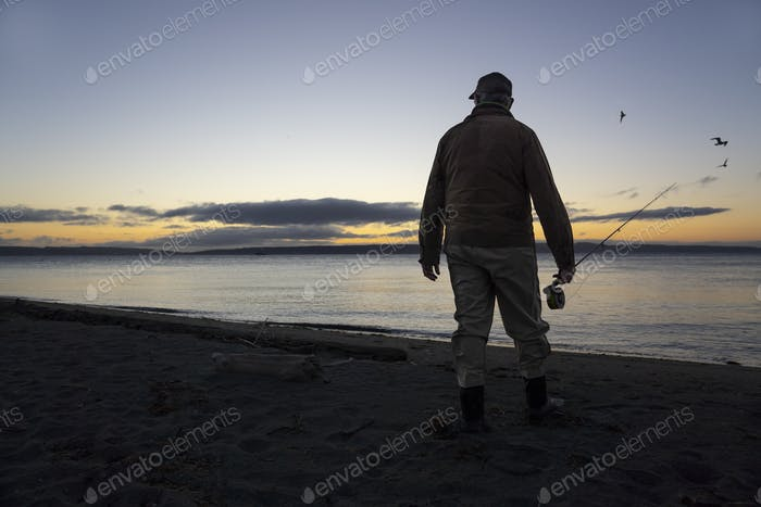 A fly fisherman gets ready to wade into salt water at sunrise and fly fish for coastal cutthroat