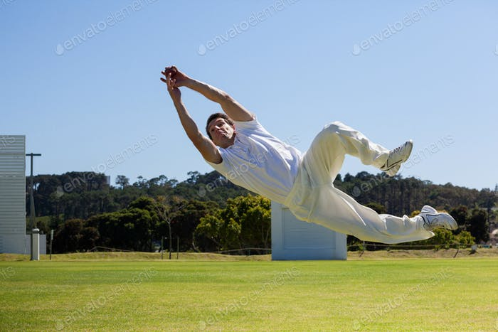 Full length of player diving to catch ball against blue sky