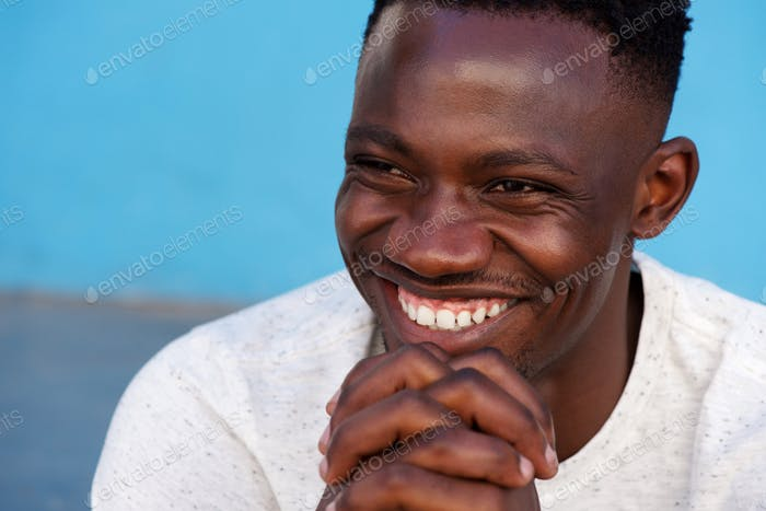 young african man smiling with hands in chin