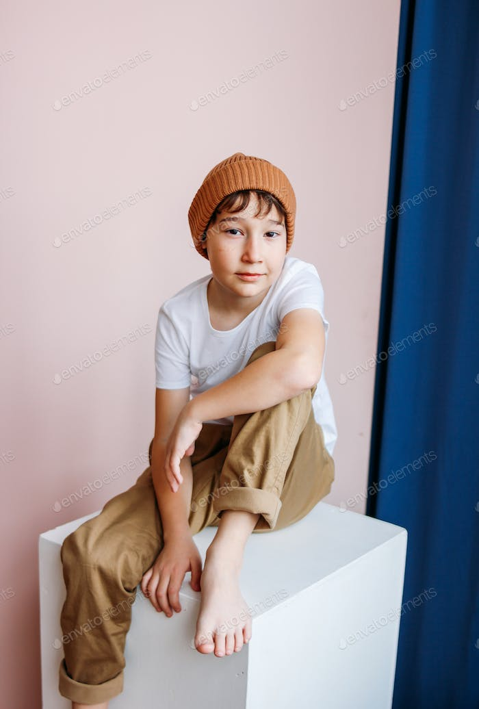 Attractive tween boy with dark hair in hat sitting on cube in studio