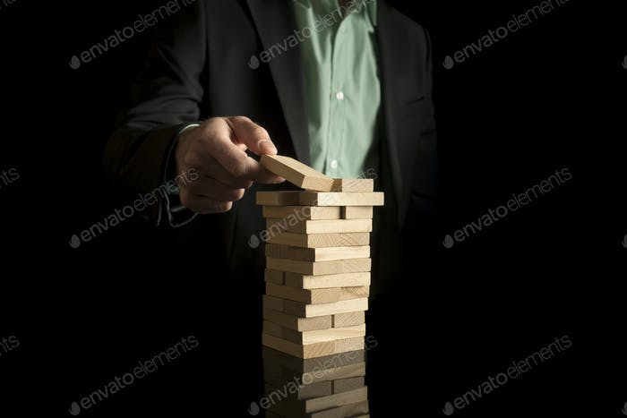 Businessman placing wooden block in a tower