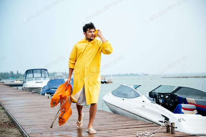 Sailor man in yellow cloak walking at the sea pier