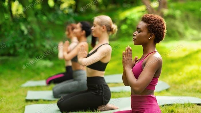 Yoga für inneren Frieden. Gruppe von multirassischen Frauen meditieren im Park im Sommer, Leerraum