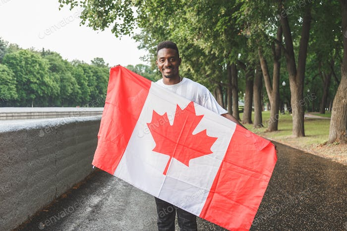 Handsome Afro American man with Canadian flag smiling at camera, standing outdoors.