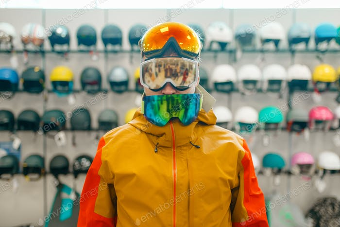 Man trying on three masks for ski or snowboarding