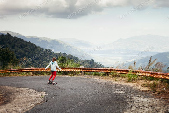 girl skateboarding in tropical jungle mountains travelling asia