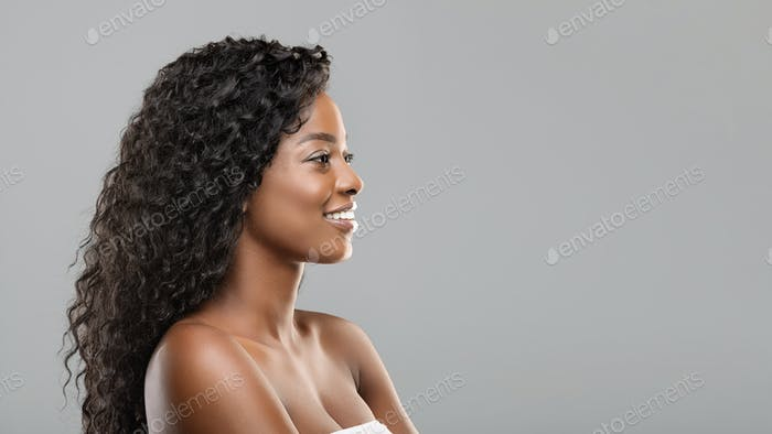 Beautiful black girl looking aside at copy space on gray background